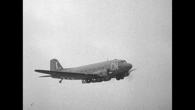 single C47 airplane flies / formation of C47s with USAAF logo visible on one nearest camera / single plane flies with ground visible below / Note...