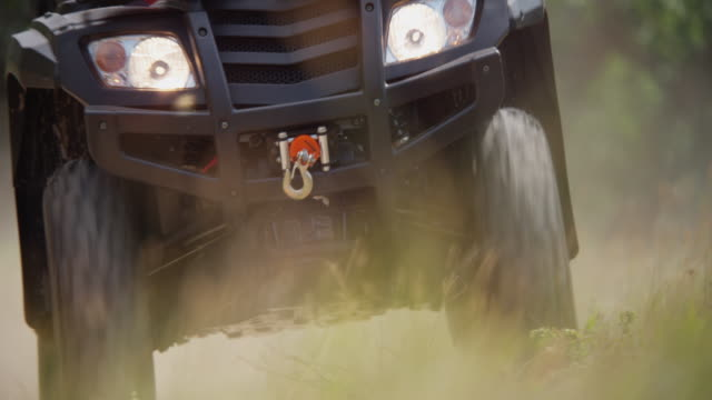 all terrain vehicle in a field approaches camera in a cloud of dust. - quadbike stock videos & royalty-free footage