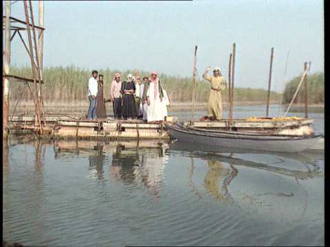 vídeos de stock, filmes e b-roll de alleged chemical attack on marsh arabs enao south lms group of marsh arabs on end of jetty set on river with marshes in b/g track back - pântano salgado