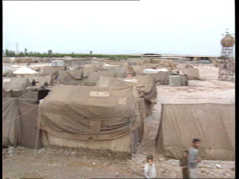 alleged chemical attack on marsh arabs itn lib tgv refugee tents pan rl on border with iran ms squalid refugee tents zoom in to people in tent - marsh stock videos & royalty-free footage