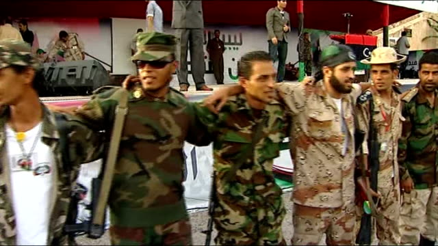 alleged mass execution of progaddafi forces in sirte tripoli group of ntc fighters stand arm in arm and giving victory sign at large rally to... - libyan civil war stock videos & royalty-free footage