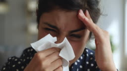 Allergic ill indian woman holding handkerchief blowing running nose