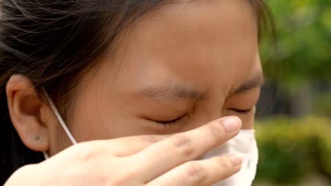 donna allergica che si gratta gli occhi perché l'inquinamento atmosferico sporco - touching video stock e b–roll