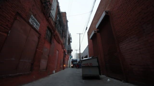 Alley With Dumpster And Homeless Man Rolling Cart And Trash Truck
