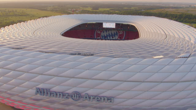 allianz arena munich drone close flight around stadium with sparkling evening sun - german culture stock videos & royalty-free footage