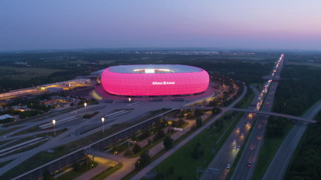 allianz arena munich drone distant dusk flight around building with highway in front - german culture stock videos & royalty-free footage