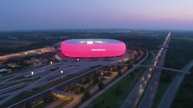 allianz arena munich drone distant dusk flight around building with highway in front - deutsche kultur stock-videos und b-roll-filmmaterial