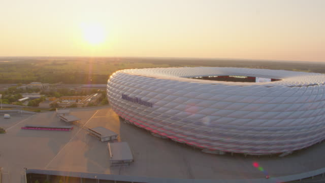 allianz arena munich drone flight away from stadium with strong sunlight - geografische lage stock-videos und b-roll-filmmaterial