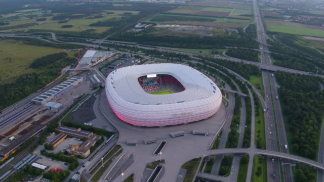 allianz arena munich drone high altitude flight over building at daybreak - geografische lage stock-videos und b-roll-filmmaterial