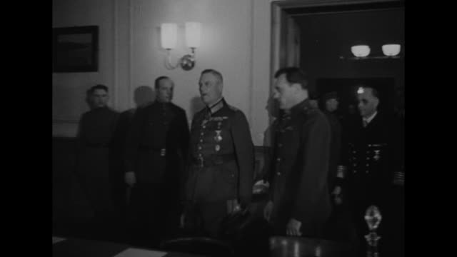 allied and soviet officers entering building where surrender will be signed us soviet and british flags over entrance / officers seated around long... - arrendersi video stock e b–roll