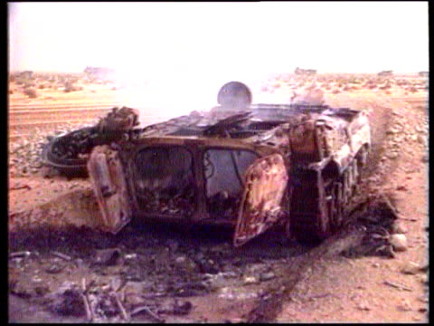 meeting lib allied armoured personnel carrier along past burning armoured vehicle burnt out armoured vehicle arab man looking at wrecked tank fielg... - 道ばた点の映像素材/bロール
