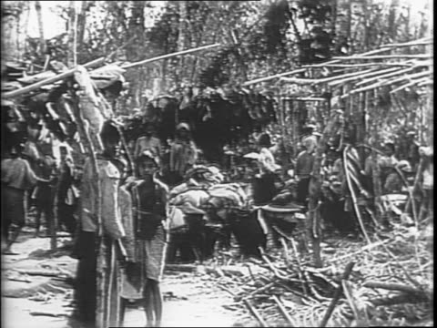 allied army soldiers standing around in muddy field next to tanks / troops marching with their gear in the wet mud next to moving tanks / montage of... - pacific war点の映像素材/bロール
