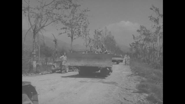 vs allied forces troops wearing doughboy helmets packs and guns walking single file on dirt road / ms bulldozers approaching on dirt road / soldiers... - prisoner walking stock videos & royalty-free footage