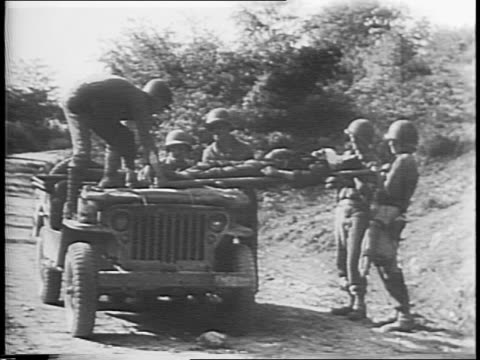 Allied infantry shooting and advancing / artillery shell hits target / troops walk past a dead German soldier on the road / montage of marching...