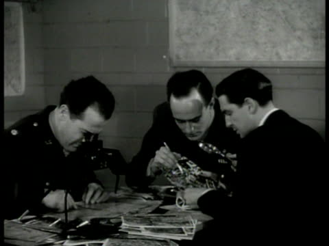 stockvideo's en b-roll-footage met allied military intelligence office men in us & british uniforms working men looking at aerial photographs pencil pointing to specific buildings... - british military