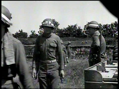 Allied military truck passing ruined German city WS Military Police walking on field CU Bulletin VS Soldiers MPs loading German refugees onto truck...