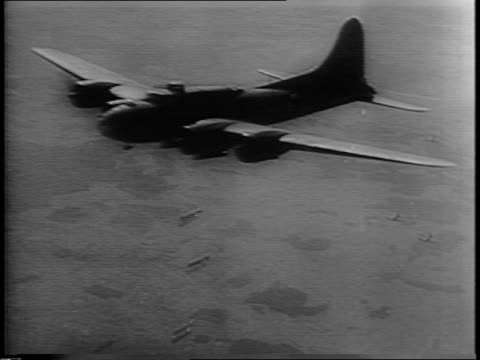 vidéos et rushes de allied planes dropping bombs on german targets / bombs exploding on the ground / men unloading a wounded man from a plane on a cot and load him into... - terrorisme