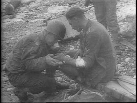 allied soldiers huddle against the cliffs of the coastline of france in dday invasion / casualties line the beach / wounded soldiers are cared for /... - invasion beach stock videos & royalty-free footage