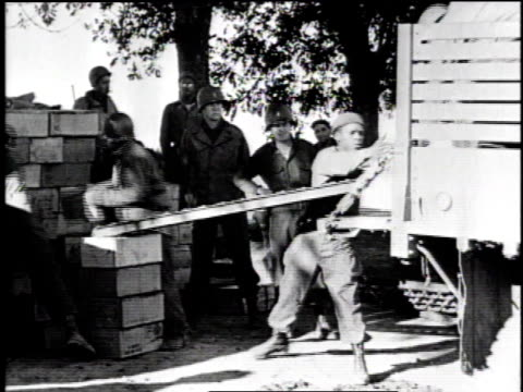 stockvideo's en b-roll-footage met allied soldiers unloading and loading supplies / supply trucks driving on road - geallieerde mogendheden