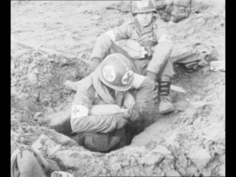 stockvideo's en b-roll-footage met allied troops and red cross medics in foxholes scattered throughout field during world war ii / soldiers wait in trench / medic in foxhole fastens... - geallieerde mogendheden