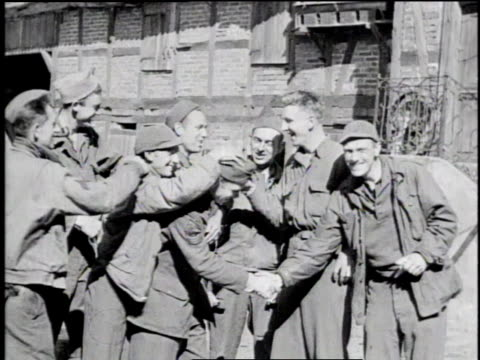 allied troops pouring from pow camp / former prisoners shaking hands and waving to passing tanks / former prisoners gather outside pow camp / germany - allied forces stock videos & royalty-free footage