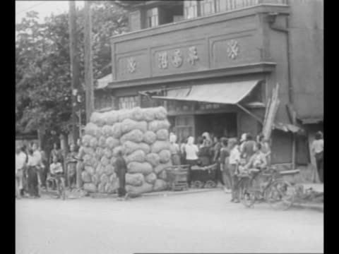 allied troops ride through japanese street as military occupation begins / military vehicles pass storefront with sandbags in front and line of... - 1940~1949年点の映像素材/bロール