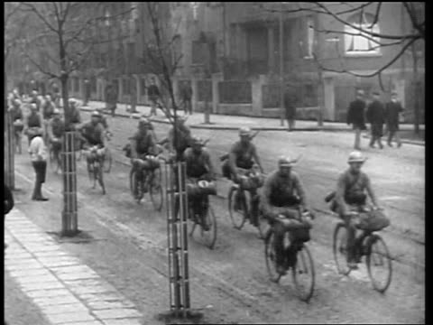 vídeos de stock e filmes b-roll de allied troops riding bicycles on city street in germany after world war i / newsreel - 1919