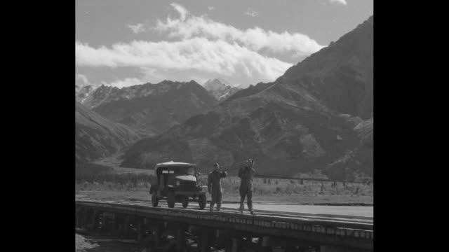 vs allterrain vehicle drives through a newly cleared area with mountains in the distance crosses a pontoon bridge passes two men carrying a wooden... - alcan highway stock videos and b-roll footage