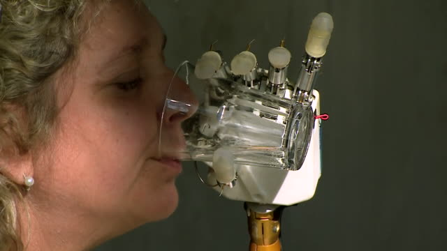 Almerina Mascarello who is testing a new bionic hand controlled by her brain demonstrates dexterity whilst using the hand to use a glass and hold...