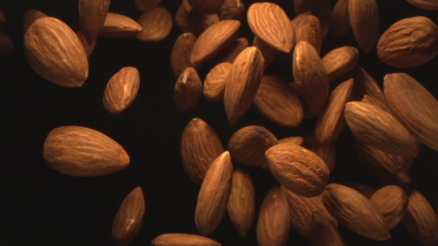 almond nuts flying in the air in a free fall in slow motion on black background at 1000 fps 4k - raw footage stock videos & royalty-free footage