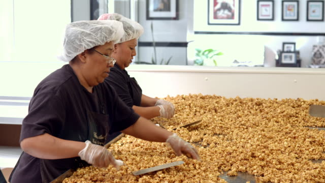 ws pan almond toffee popcorn on large stainless steel table being mixed and spread out by female workers / rancho mirage, california, usa - アーモンド点の映像素材/bロール