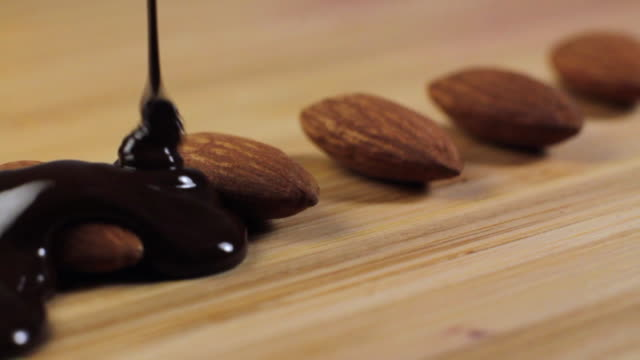 vídeos de stock e filmes b-roll de slo mo cu almonds being covered in melted chocolate - fruto seco