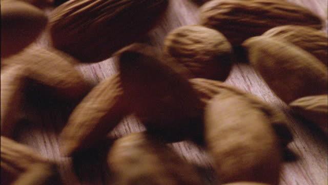 ecu, almonds falling on table top - アーモンド点の映像素材/bロール
