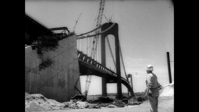 / almost completed bridge spanning the narrows at the port of new york / different angles of the bridge's structure / workers using cranes to... - 1964 stock videos & royalty-free footage