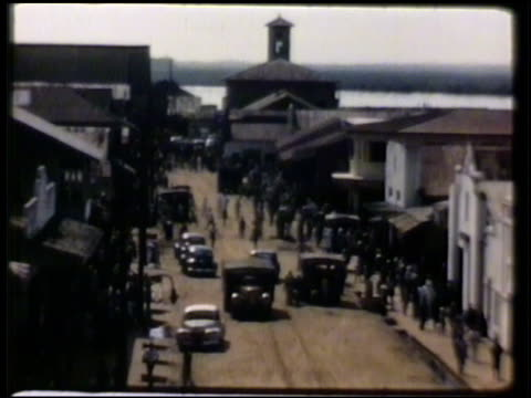 vídeos y material grabado en eventos de stock de almost silhouette of crowded city street w/ vehicles pedestrians ws straw hut homes lined up on hillside vs liberians outside straw house female... - liberia