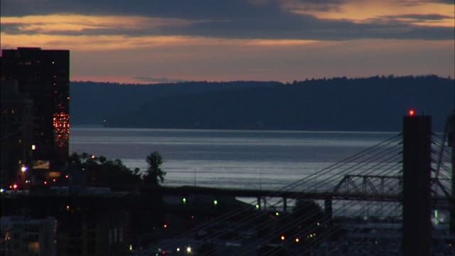 almost silhouette of partial downtown tacoma buildings bridge lower frame fg commencement bay bg w/ silhouette of other side of shore distant bg wa - pierce county washington bildbanksvideor och videomaterial från bakom kulisserna