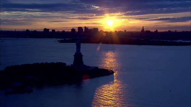 vídeos de stock e filmes b-roll de almost silhouette of statue of liberty on liberty island silhouette of governor's island brooklyn skyline bg bright yellow orange sun in clouds bg - statue of liberty new york city