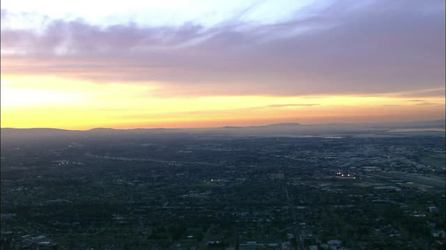 sunset hd aerial ** xws almost silhouette of unidentifiable cityscape stretching toward unidentifiable silhouette of mountain bg bright white yellow... - san jose california stock videos & royalty-free footage