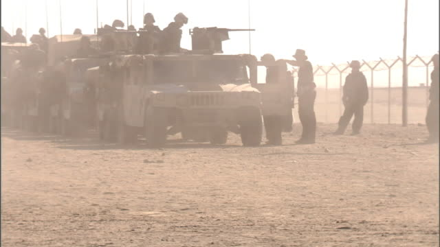 ws almost silhouette of unidentifiable soldiers amp humvees parked on desert base w/ sand kicking up fg military jeep driving through frame fg middle... - 4x4 stock videos & royalty-free footage