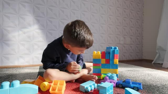 alone child playing with building blocks - tvåbarnsfamilj bildbanksvideor och videomaterial från bakom kulisserna