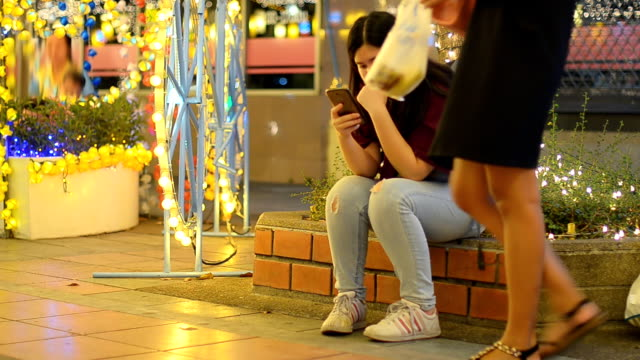 alone woman using smartphone in celebration event at night - metrosexual stock videos & royalty-free footage