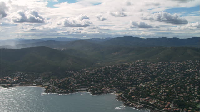vidéos et rushes de aerial along green, hilly coastline with houses/ var, france - var