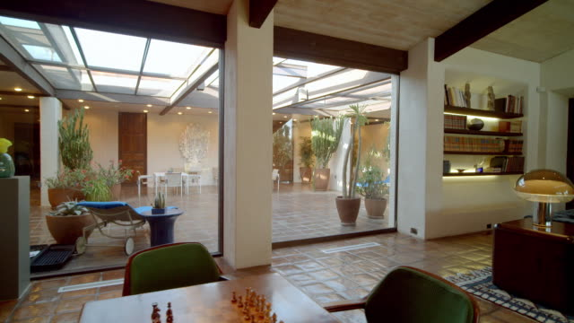 ts along large windows opening view from living room to covered atrium in mid-century modern home - ソファ点の映像素材/bロール