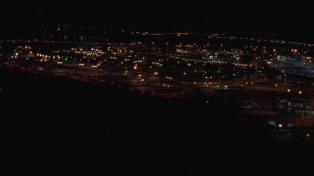 LOW AERIAL along Potomac River and Ronald Reagan Washington National Airport at night, Washington DC, Washington, USA