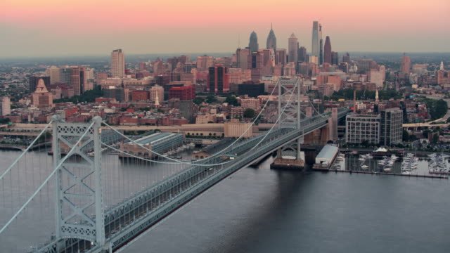 aerial along the benjamin franklin bridge over delaware river in philadelphia - center city philadelphia stock videos and b-roll footage