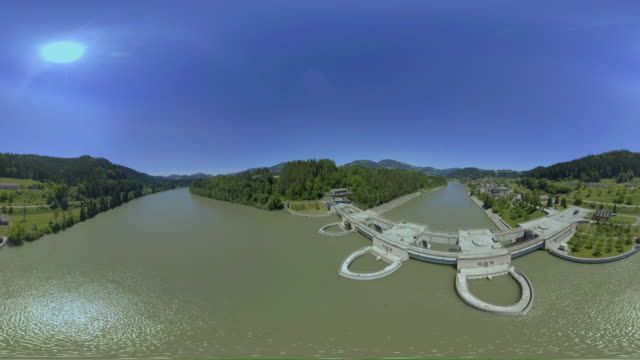 AERIAL VR 360: Along the river bank at the hydroelectric power plant in sunshine