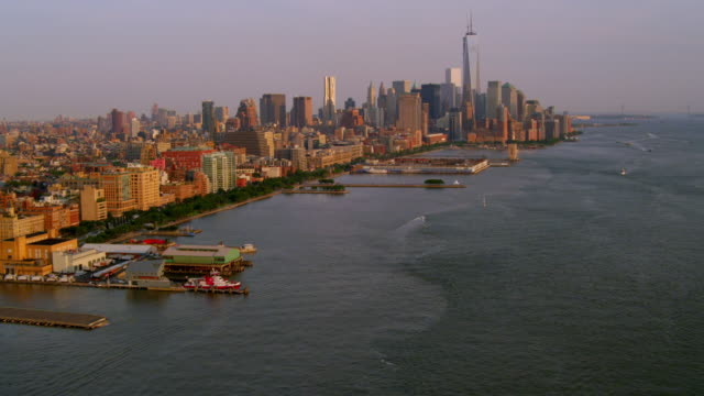 long aerial along west side waterfront with tilt up to lower manhattan skyline and zoom in to new york by gehry - woolworth building stock videos & royalty-free footage