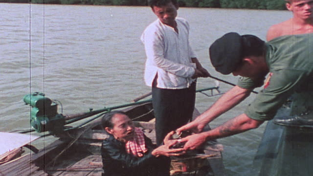 pbr alongside sampan with soldiers returning identification cards speaking with sampan crew members and passing out cigarettes and candy / vietnam - sampan stock videos & royalty-free footage