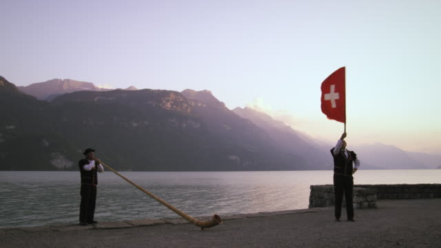 Alphorn player and flag thrower perform near lake