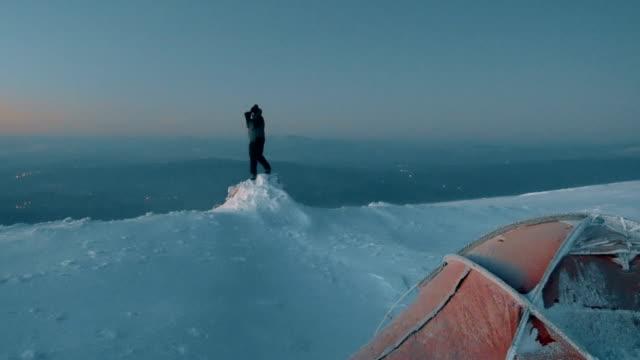 stockvideo's en b-roll-footage met alpine klimmer is fotograferen in de piek van de berg van grote hoogte in de winter bij zonsopgang - tent